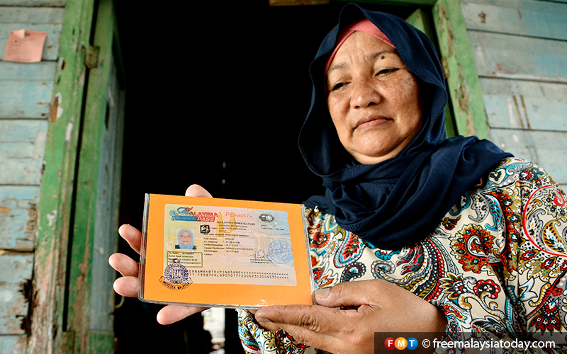 Resident Pernama Pinasang, from Tawi-Tawi Island in the southern Philippines, shows her IMM13 immigration pass, issued to those who fled the conflict in Mindanao in the 1970s.