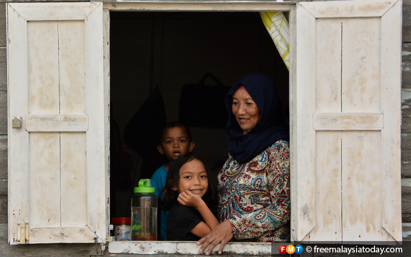 Pernama, her nephew and niece looking out the window of their simple house.