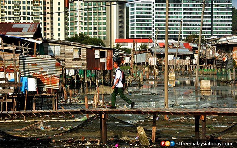A schoolboy walks on the rickety bridge that connects homes at Kampung Sembulan Tengah against a backdrop of Kota Kinabalu's modern apartments.