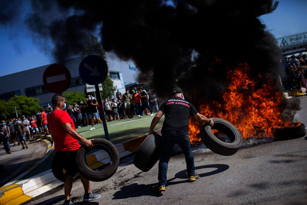 Nissan workers burn tyres, blockade factory after closure announcement