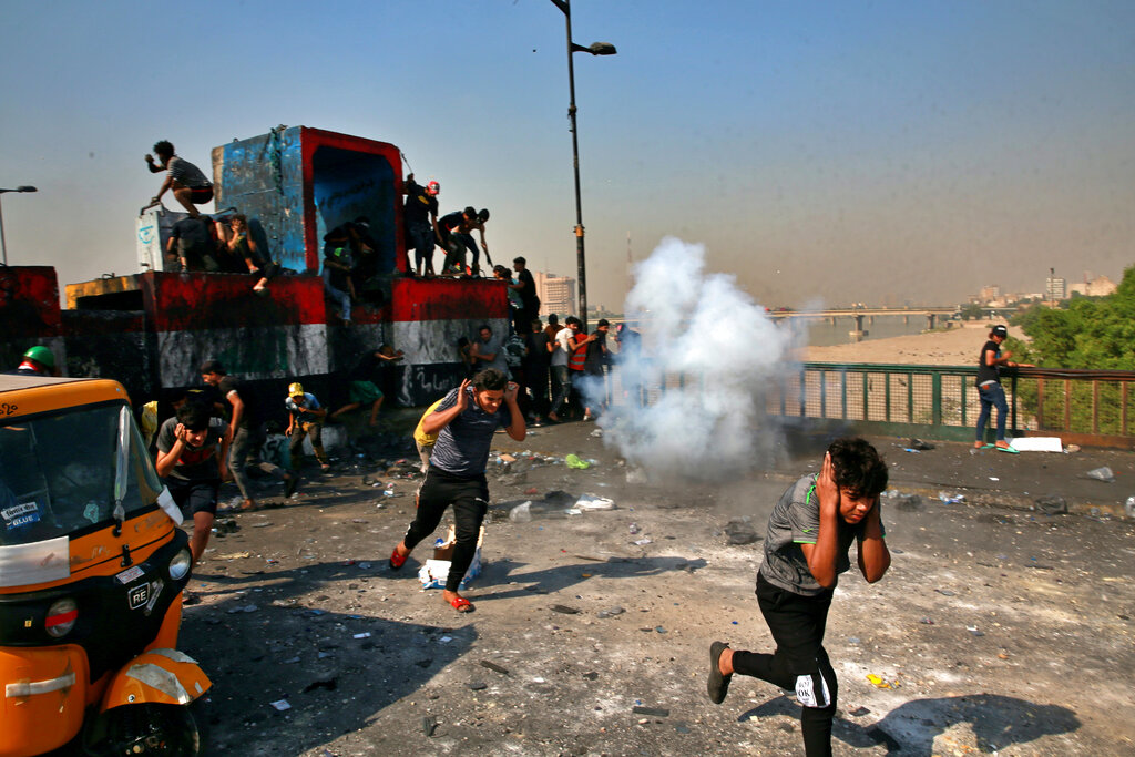 Protesters, police clash again in Iraq a year after uprising