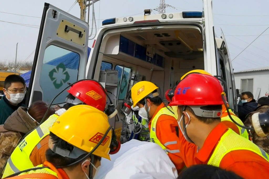 Rescuers carry a miner into an ambulance in Shandong yesterday
