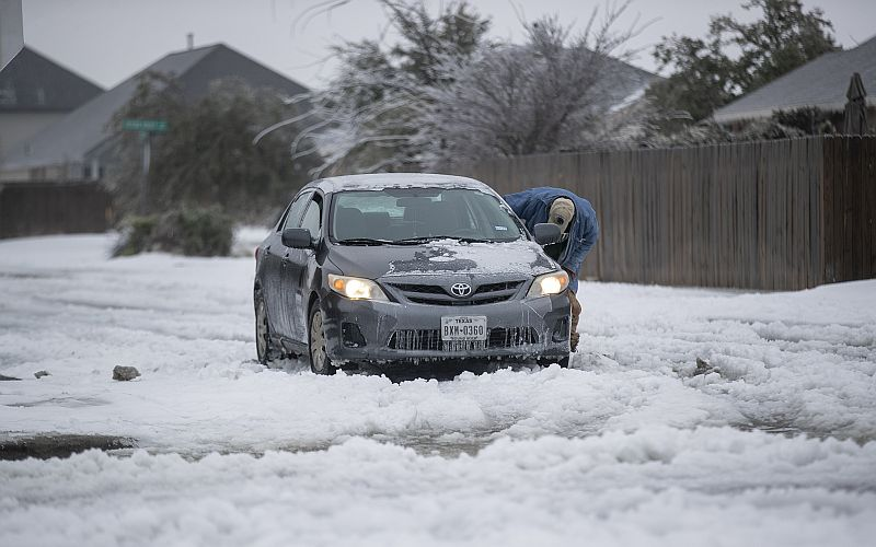 A vehicle is stuck on a snow-covered road in Austin on Wednesday